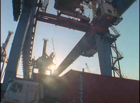 A massive crane moves shipping containers at a port while cargo trucks move underneath Footage
