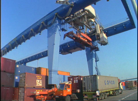A huge crane picks up and moves cargo containers in a port Stock Video Footage