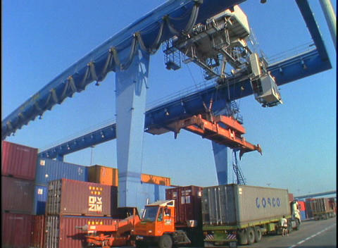 A huge crane picks up and moves cargo containers in a port Footage