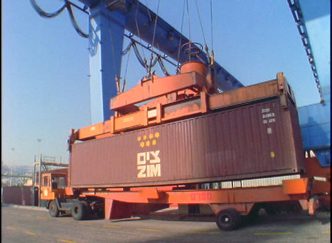 A crane lifts a large cargo container from the back of a flatbed truck Footage