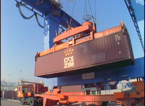 A crane lifts a large cargo container from the back of a... Stock Video Footage