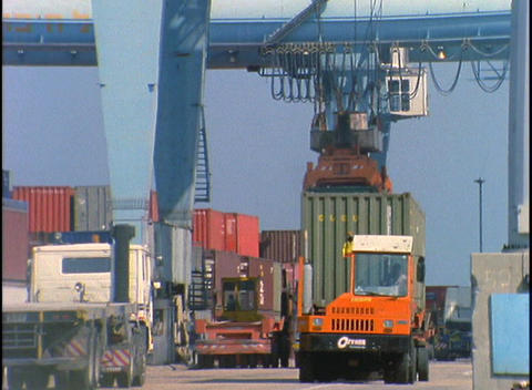Vehicles move about a port facility while a large crane... Stock Video Footage