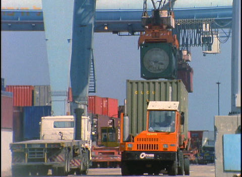 Vehicles move about a port facility while a large crane moves cargo overhead Live Action