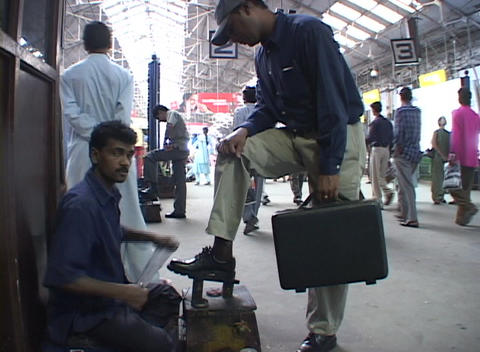 People exit a commuter train at Bombay's Victoria station as a man gets a shoeshine Footage