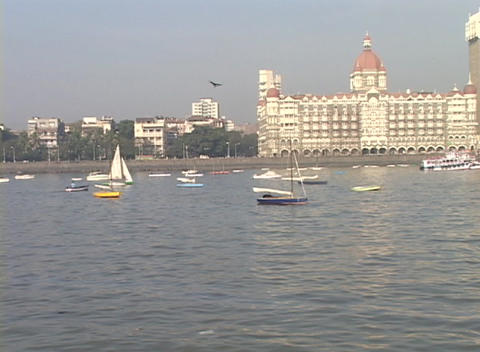 A pan across from boats in the harbor to the Taj Mahal Hotel in Bombay, India Footage