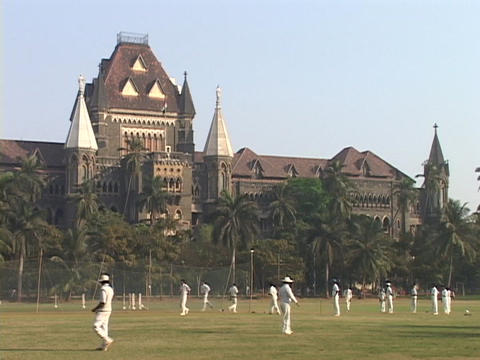 Cricket players practice in front of a Victorian government building in Bombay, India Footage