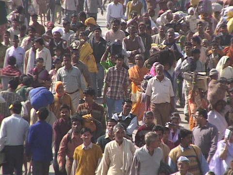 A mass of pedestrians walks down a street in India Live Action