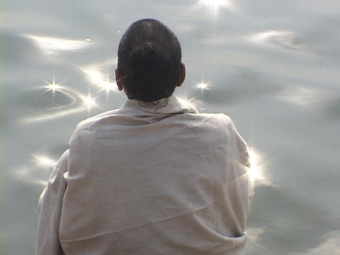 A contemplative Hindu pilgrim at a sparkling river Footage