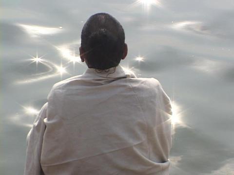 A contemplative Hindu pilgrim at a sparkling river Footage