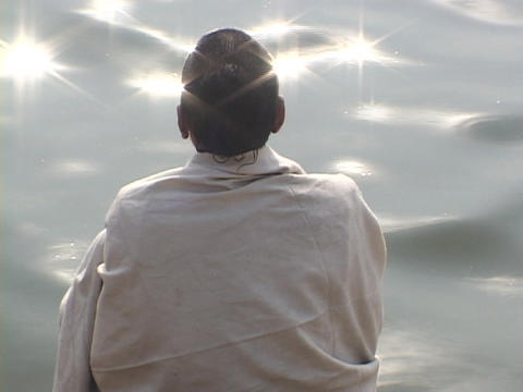 A contemplative Hindu pilgrim at a sparkling river Stock Video Footage