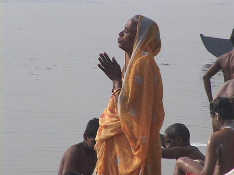 An Indian woman prays next to the Ganges as men nearby bathe in the river Footage
