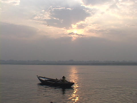 A man rows a boat against a pale sky on the Ganges River Stock Video Footage