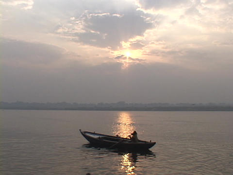 A man rows a boat against a pale sky on the Ganges River Footage