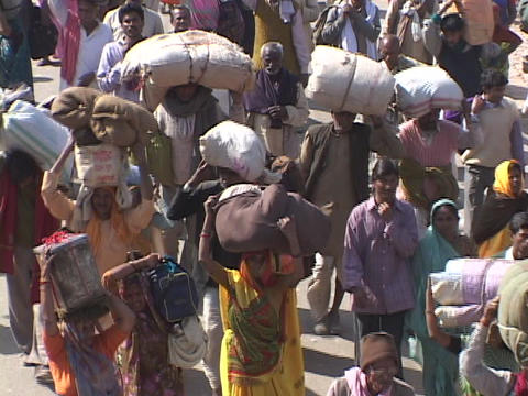 Large crowds of people walk on the road in India Stock Video Footage