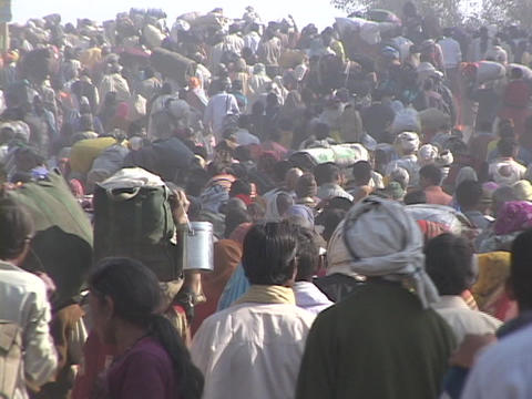Huge crowds of people walk on a road in India Stock Video Footage