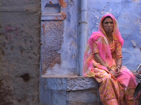 A woman sits in colorful clothing in a blue alley way in Jodhpur, India Live Action
