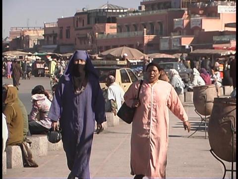 Pedestrians walk down the street in Marrakesh, Morocco Stock Video Footage