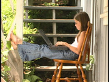 A girl works on laptop computer on a porch Footage