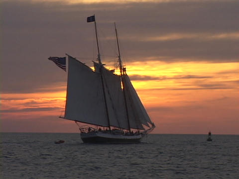 Large sailboat or clipper ship, sails toward the horizon during golden hour Footage