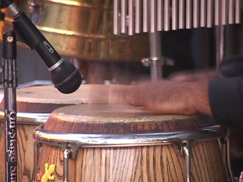 A man's hands play a set of bongo drums Footage