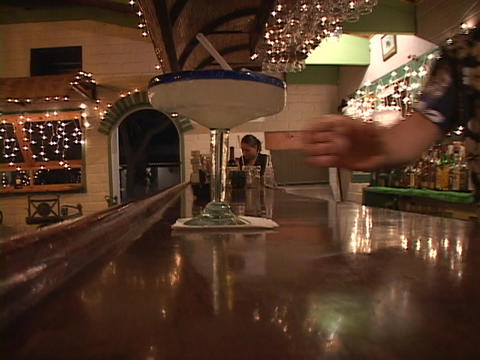 A male bartender serves a patron a large Margarita Footage