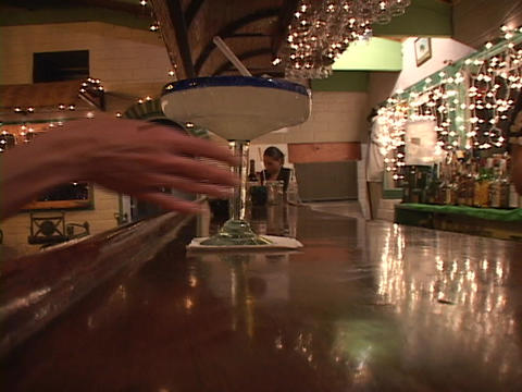 A male bartender serves a patron a large Margarita Stock Video Footage