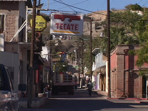 A few pedestrians walk a street in a rural town in Mexico Stock Video Footage
