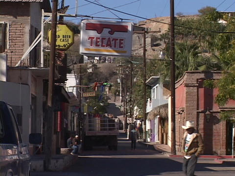 A few pedestrians walk a street in a rural town in Mexico Stock Video Footage