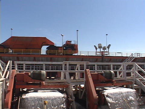 A large truck passes over two conveyors on a salt farm Stock Video Footage