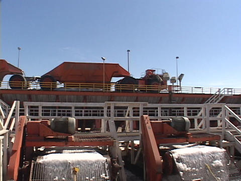 A large truck passes over two conveyors on a salt farm Footage