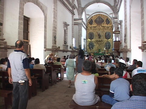 Patrons of a Mexican Catholic Church walk in and sit among the pews Footage
