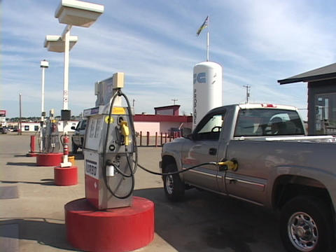 A truck fills up at the gas pump Live Action