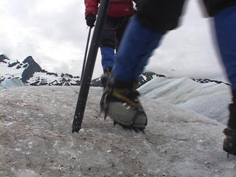 Four ice hikers walk off a round knob of ice Footage