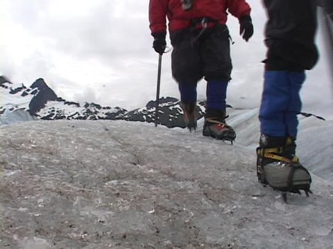 Four ice hikers walk off a round knob of ice Stock Video Footage