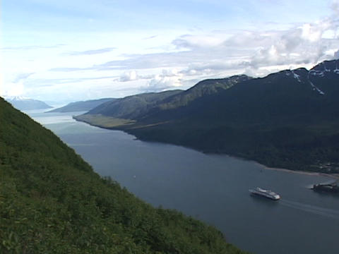 A cruise ship travels in an Alaskan fjords Live Action