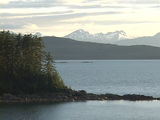 An island rests in a lake before snow dusted mountains Stock Video Footage