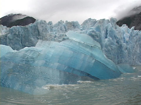 A blue iceberg floats in water Stock Video Footage