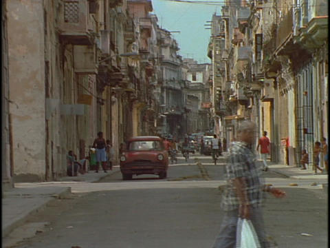 Vintage cars travel on a pedestrian filled street among the architecture of downtown Havana, Cuba Footage