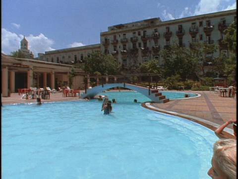 Sunbathers and swimmers hang out at the pool of a resort Footage