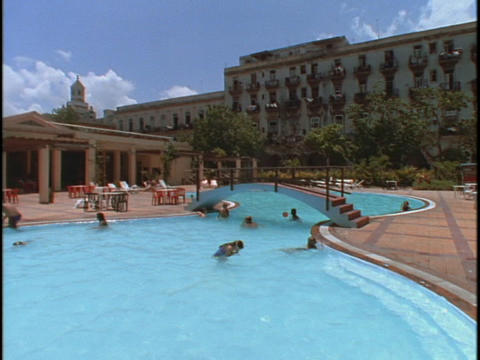 Sunbathers and swimmers hang out at the pool of a resort Stock Video Footage