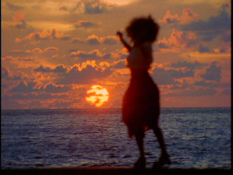 A woman shakes her stuff in front of the ocean during a beautiful golden-hour Footage