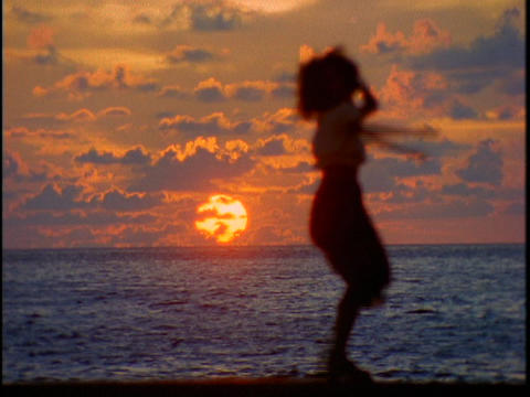A woman shakes her stuff in front of the ocean during a... Stock Video Footage