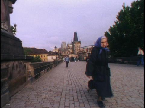 A peasant woman in Czech Slovak republic crosses a bridge in Prague Footage