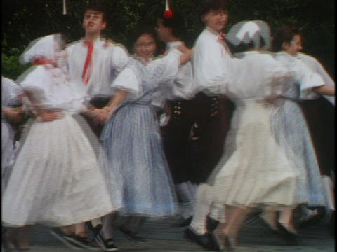 Traditional dancers in Prague dance together in a circle holding hands Footage