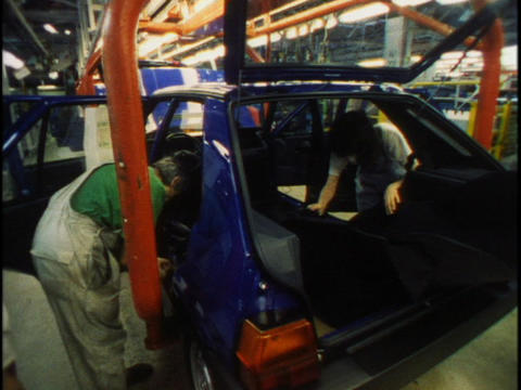 Men and women work together on an auto assembly line Footage