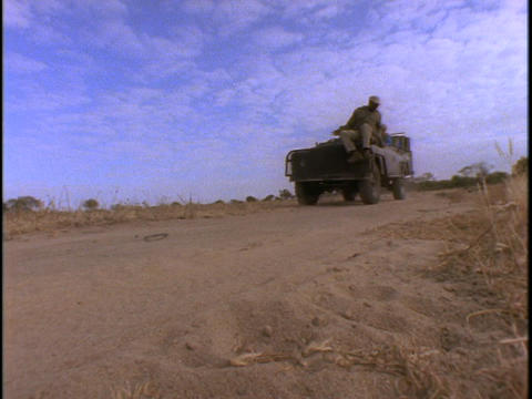 A group of men sit in an open air Jeep traveling on a sandy road in Kenya Live Action