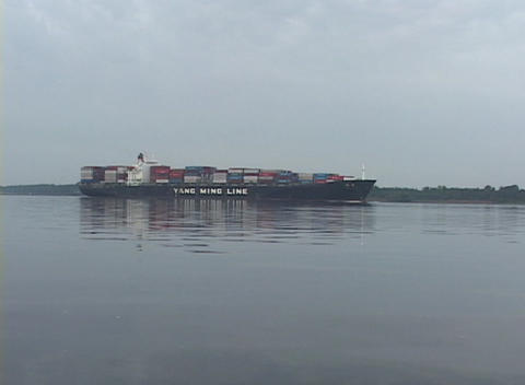 A large trash barge floats slowly across the water Footage