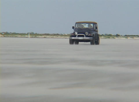 A jeep drives through a low dust storm Live Action