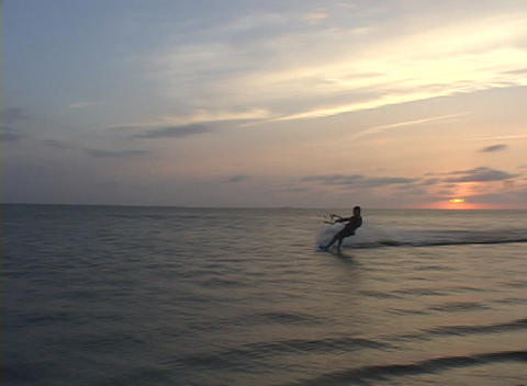 A windsurfer speeds across the water near the shore Footage