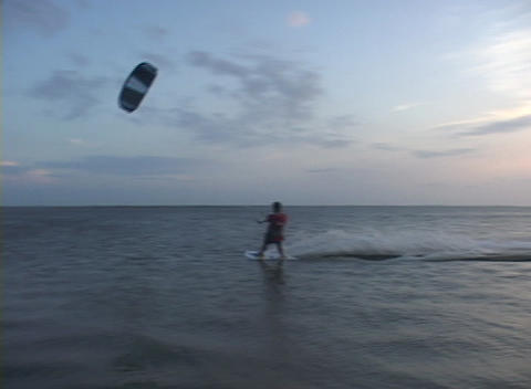 A windsurfer speeds across the water near the shore Stock Video Footage